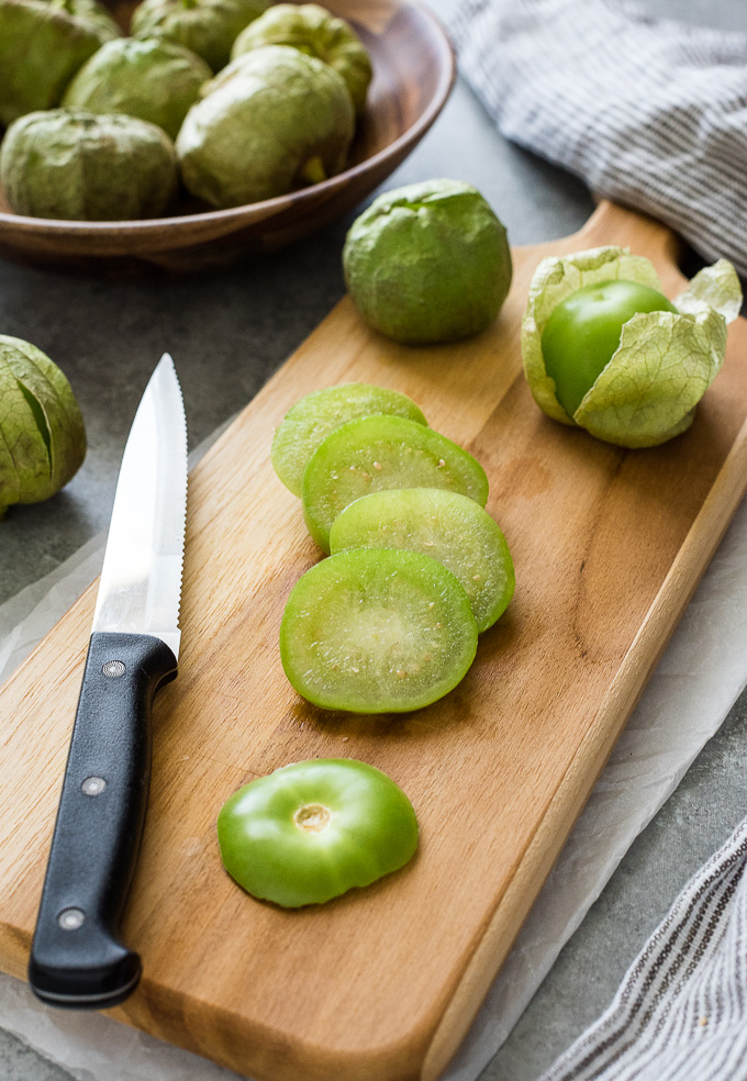 Sliced tomatillo on a cutting board with a knife