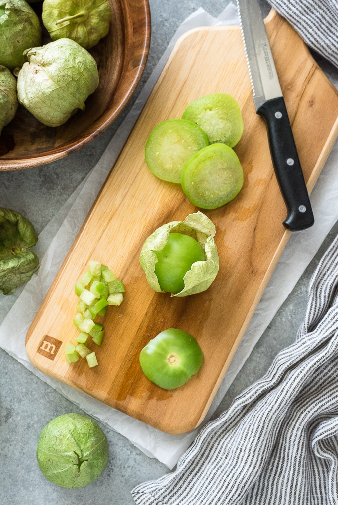 Diced, sliced and whole tomatillos on a cutting board
