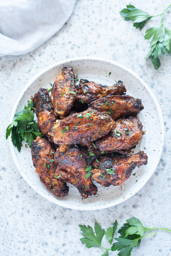 Air fryer chicken wings on a white plate with sprig of parsley