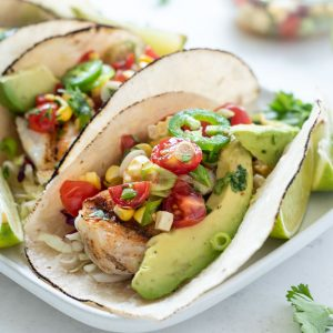 Grilled Fish Taco topped with cherry tomato salsa and avocado