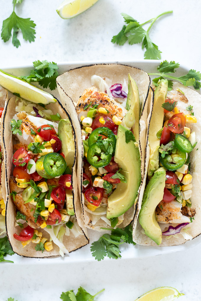 Cod fish tacos topped with salsa, avocado and jalapeno