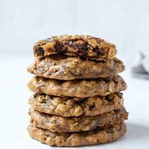 Stack of peanut butter banana oatmeal cookies with top cookie in half