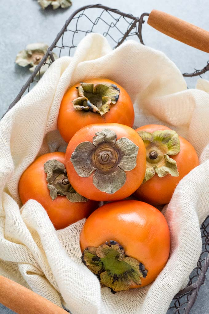 Fuyu persimmons in a wire basket
